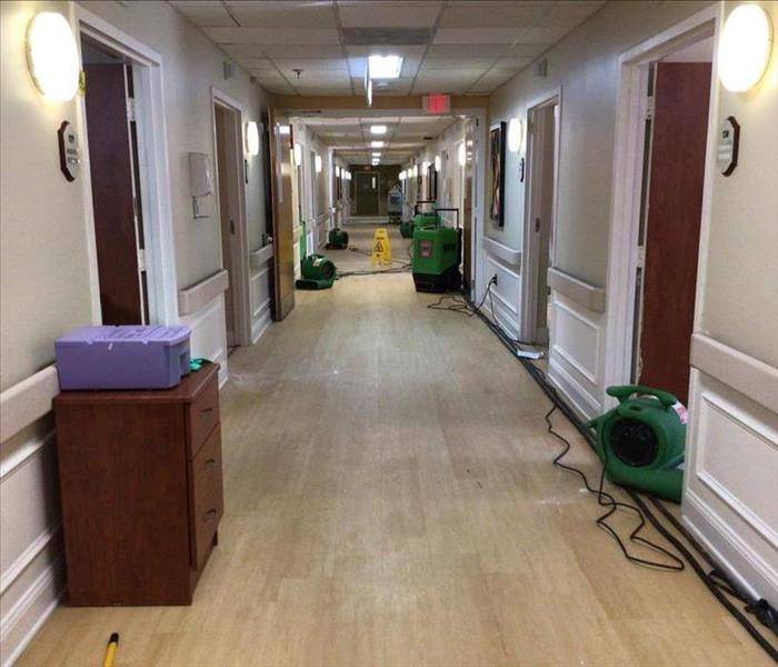 medical facility hallway with green water drying equipment