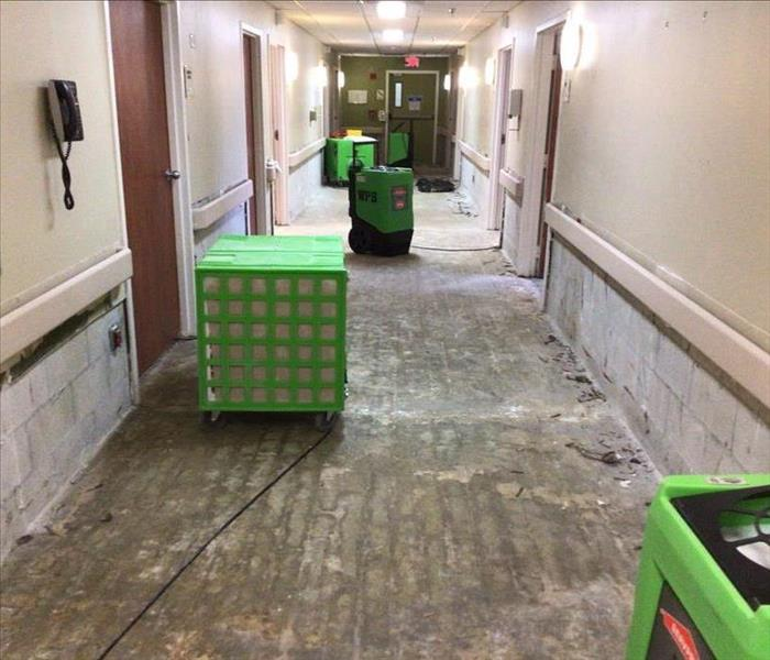 medical facility hallway post demolition with no drywall or flooring and green equipment set up
