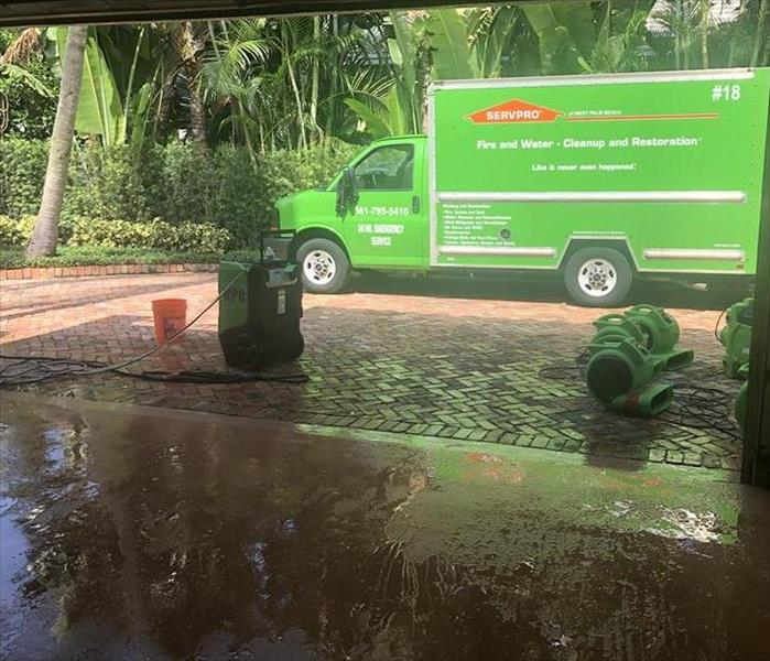 Garage with wet floor and SERVPRO green truck outside.
