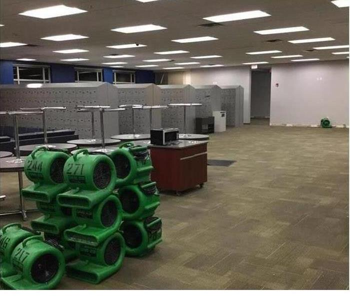 A commercial office with multiple SERVPRO air movers on the floor