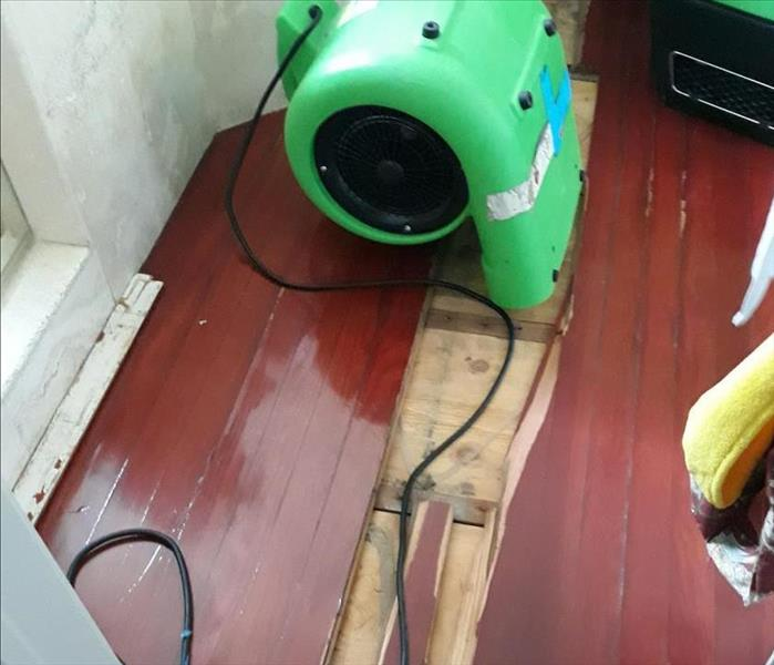 air mover on floor boards drying out water after a flood